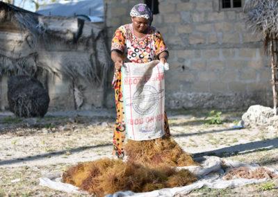 Dès son arrivée chez elle, dans la cour, Aïcha sèche les algues au soleil